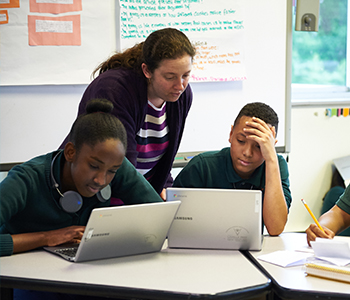 A teacher helping students with classwork
