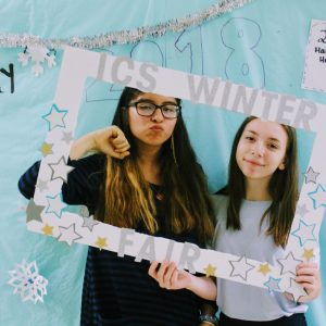 Two students holding up a event frame